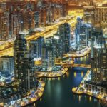 Fantastic rooftop skyline: illuminated architecture of a big city. Dubai Marina by night, United Arab Emirates.