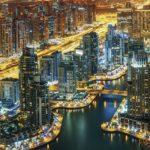 Fantastic rooftop skyline: illuminated architecture of a big city. Dubai Marina by night, United Arab Emirates.