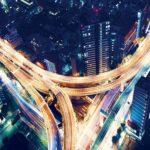 Aerial view of a massive highway intersection at night in Shinjuku, Tokyo, Japan
